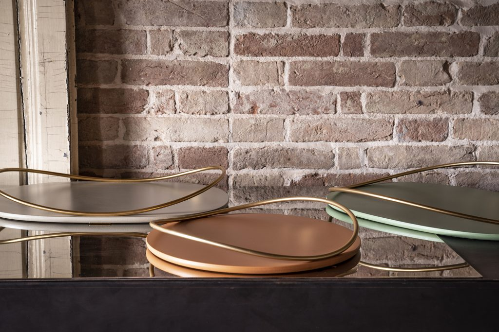 Photo of Touché trays in cotto, taupe and sage green with 24k gold gavanized handle by Mason Editions